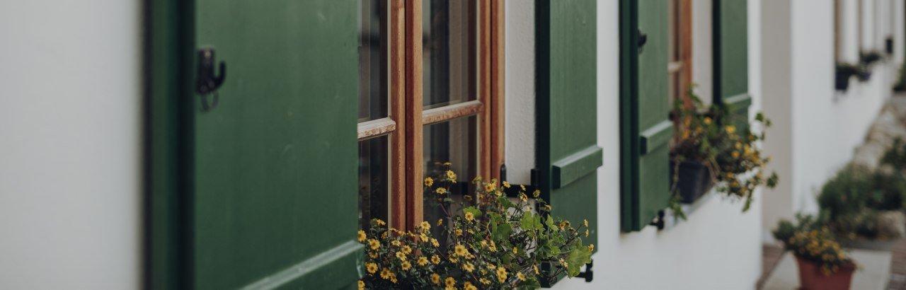grüne Fensterläden und Blumen schmücken den sanierten Althof der Eigentümergemeinschaft Immenthal © Allgäu GmbH, Philip Herzhoff